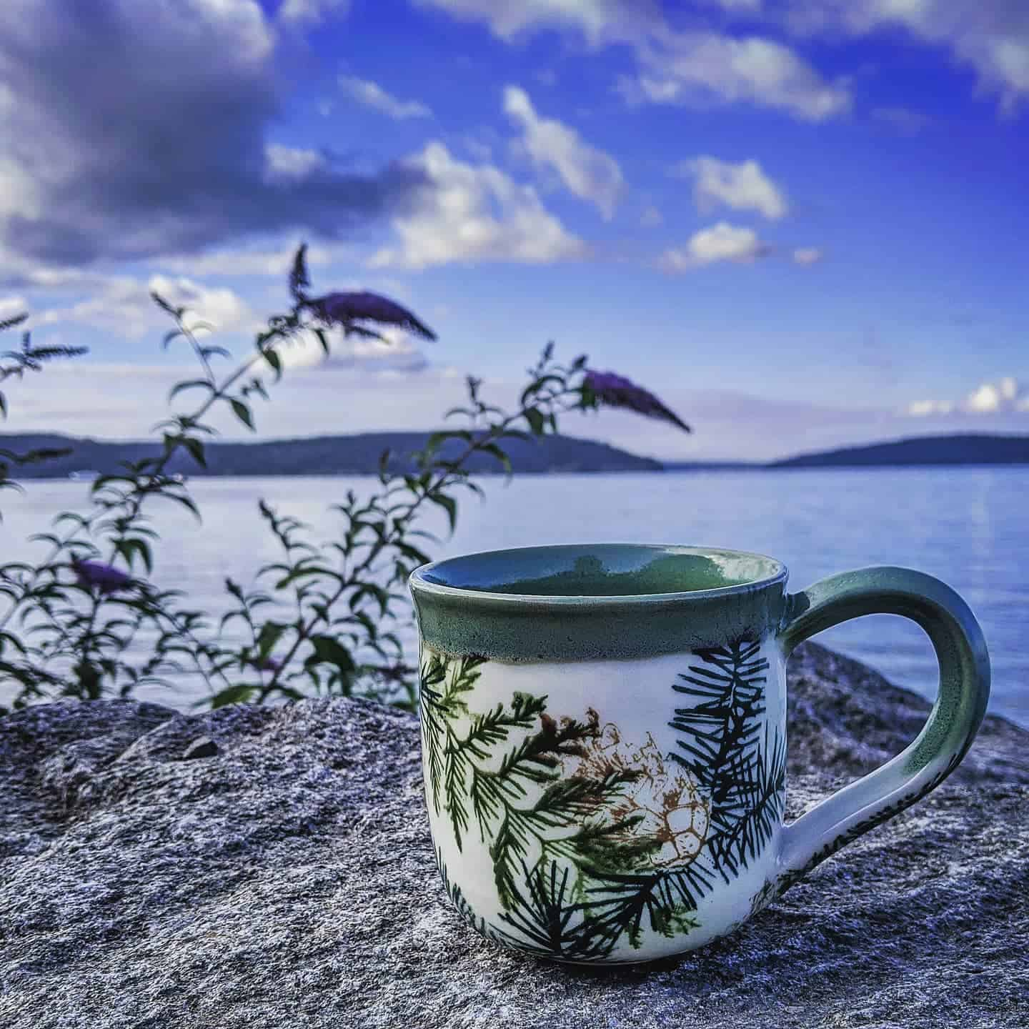 handmade pottery mug on a rock
